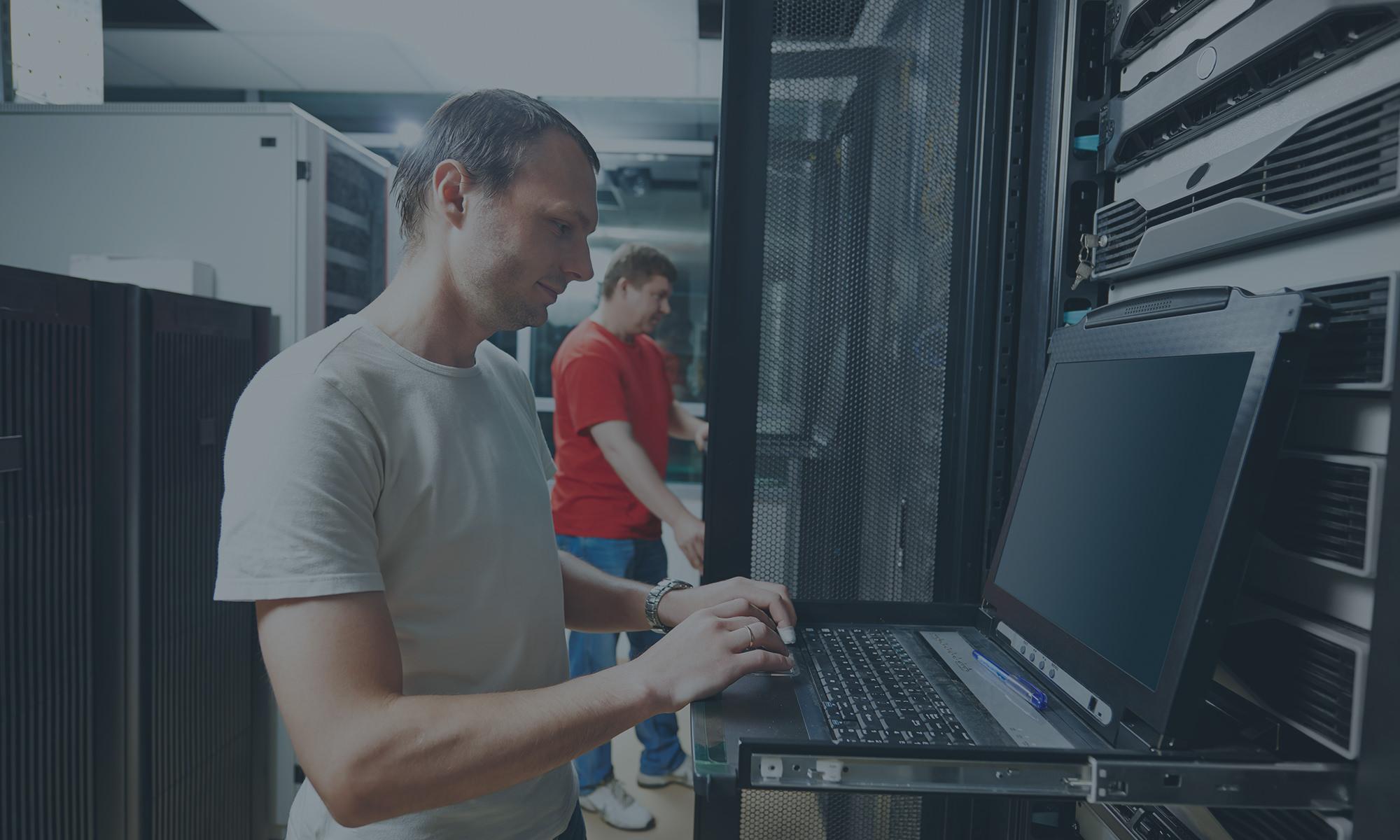 Man typing on laptop in server room